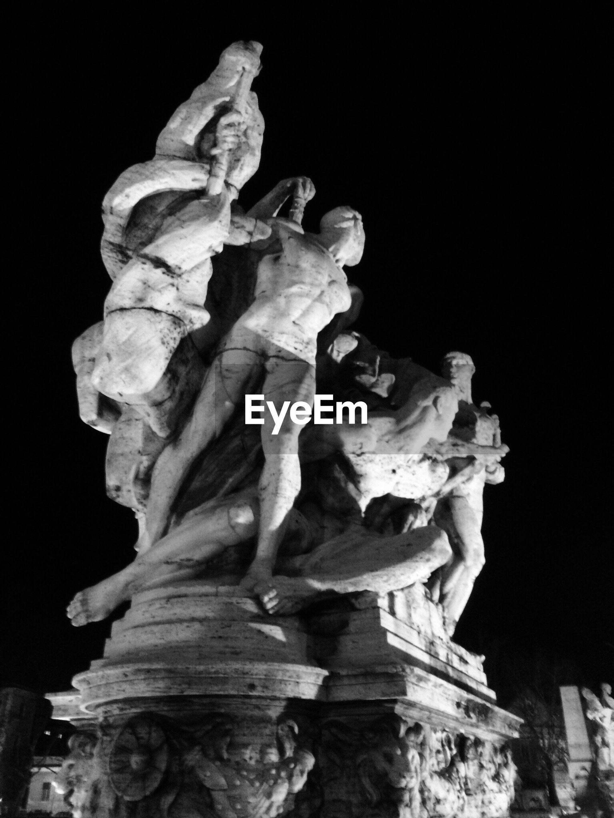 Low angle view of sculpture against clear sky at night