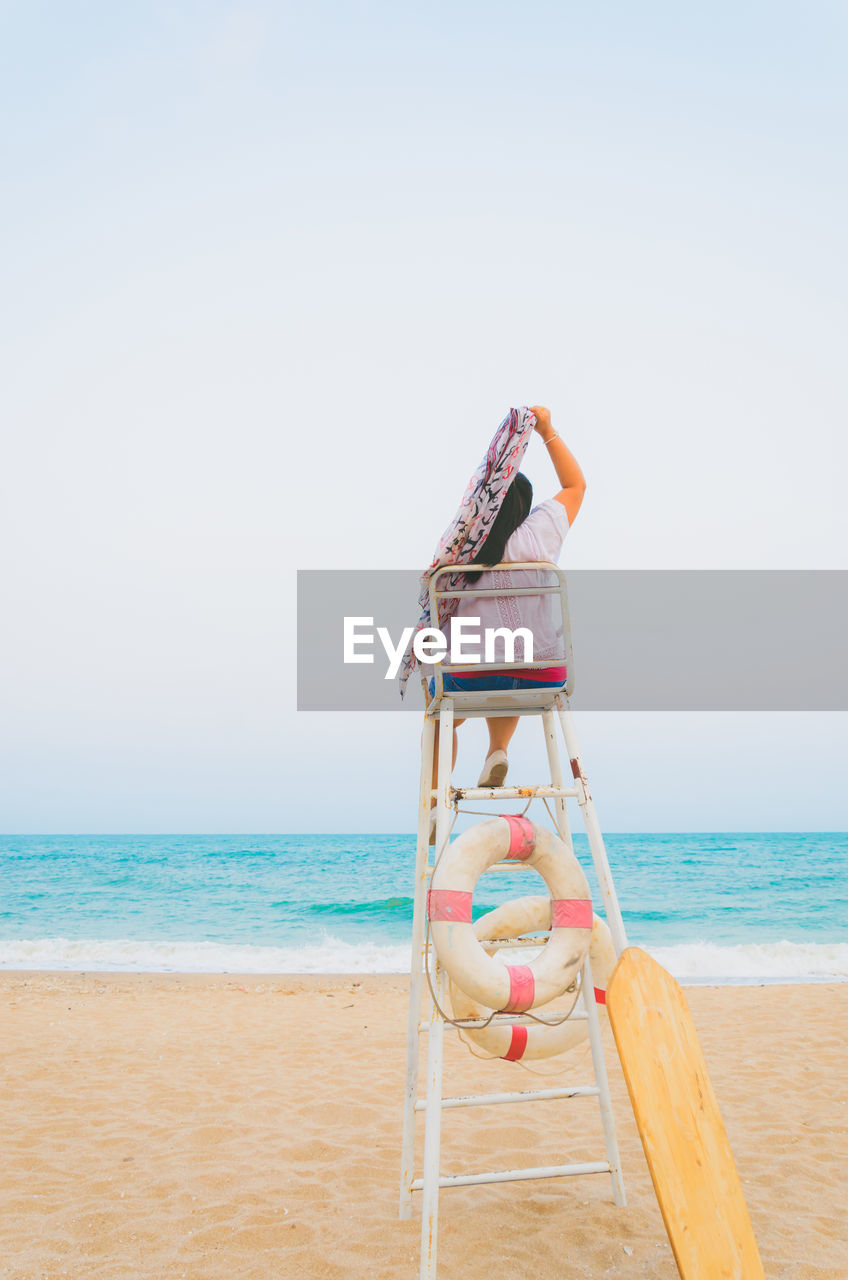 Rear view of woman with scarf sitting on lifeguard chair at beach against clear sky