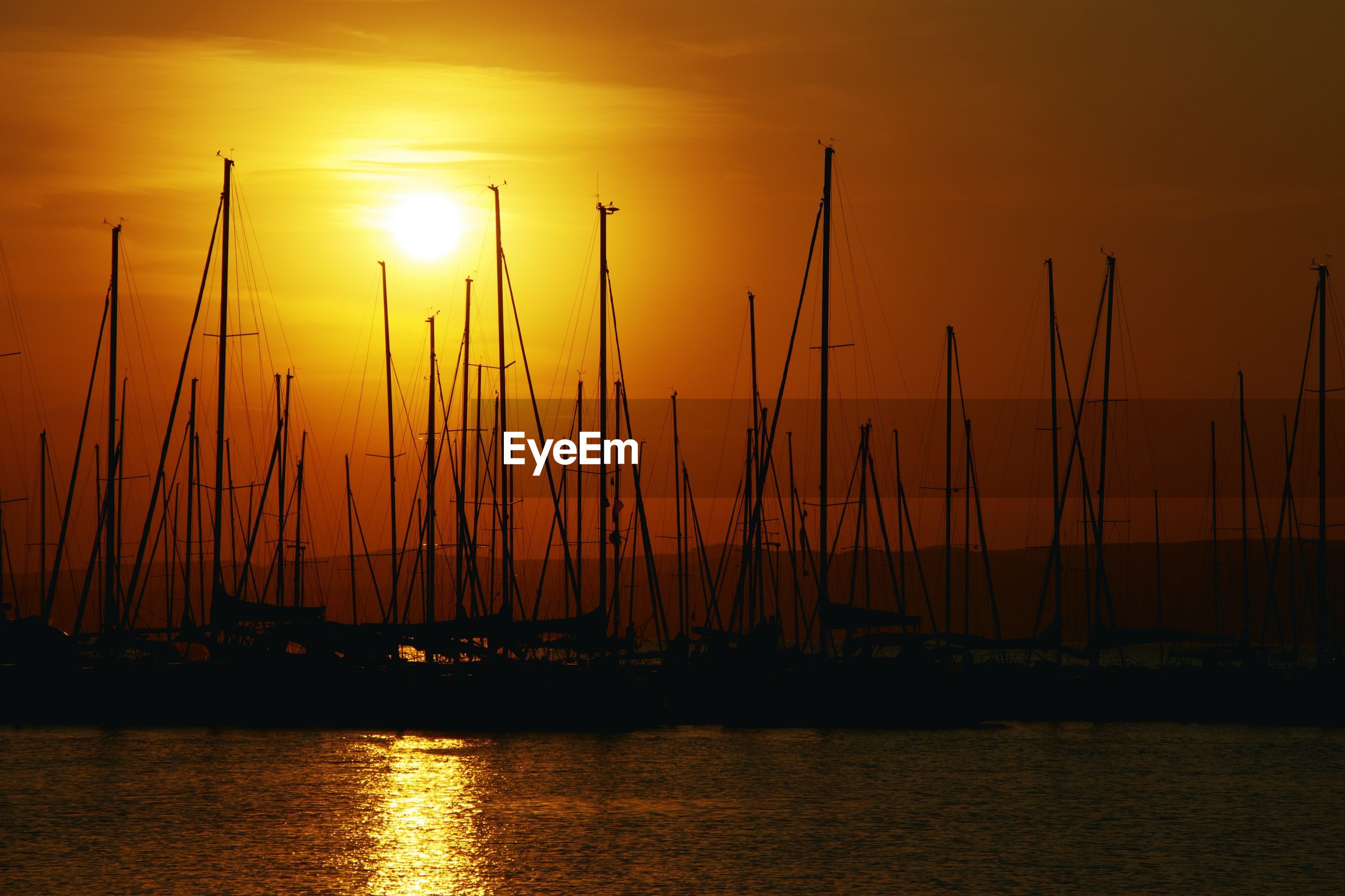 SAILBOATS ON SEA AGAINST ORANGE SKY