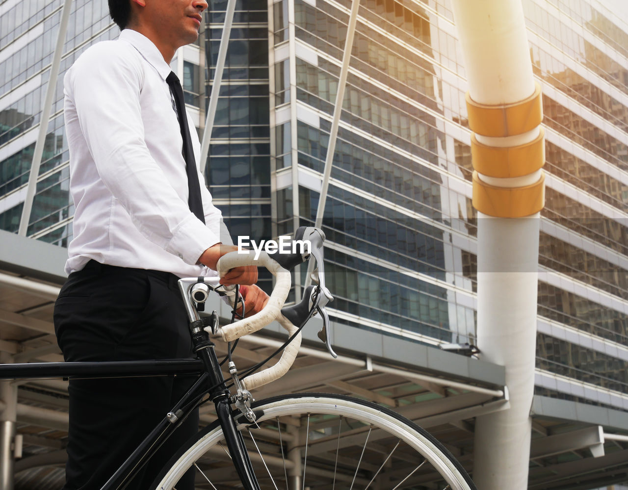 men, one person, real people, bicycle, midsection, transportation, mode of transportation, three quarter length, lifestyles, land vehicle, males, occupation, business, standing, clothing, holding, formalwear, ride, focus on foreground, riding