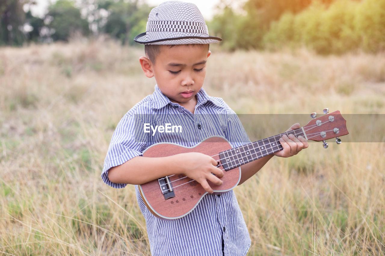 Boy playing guitar on field