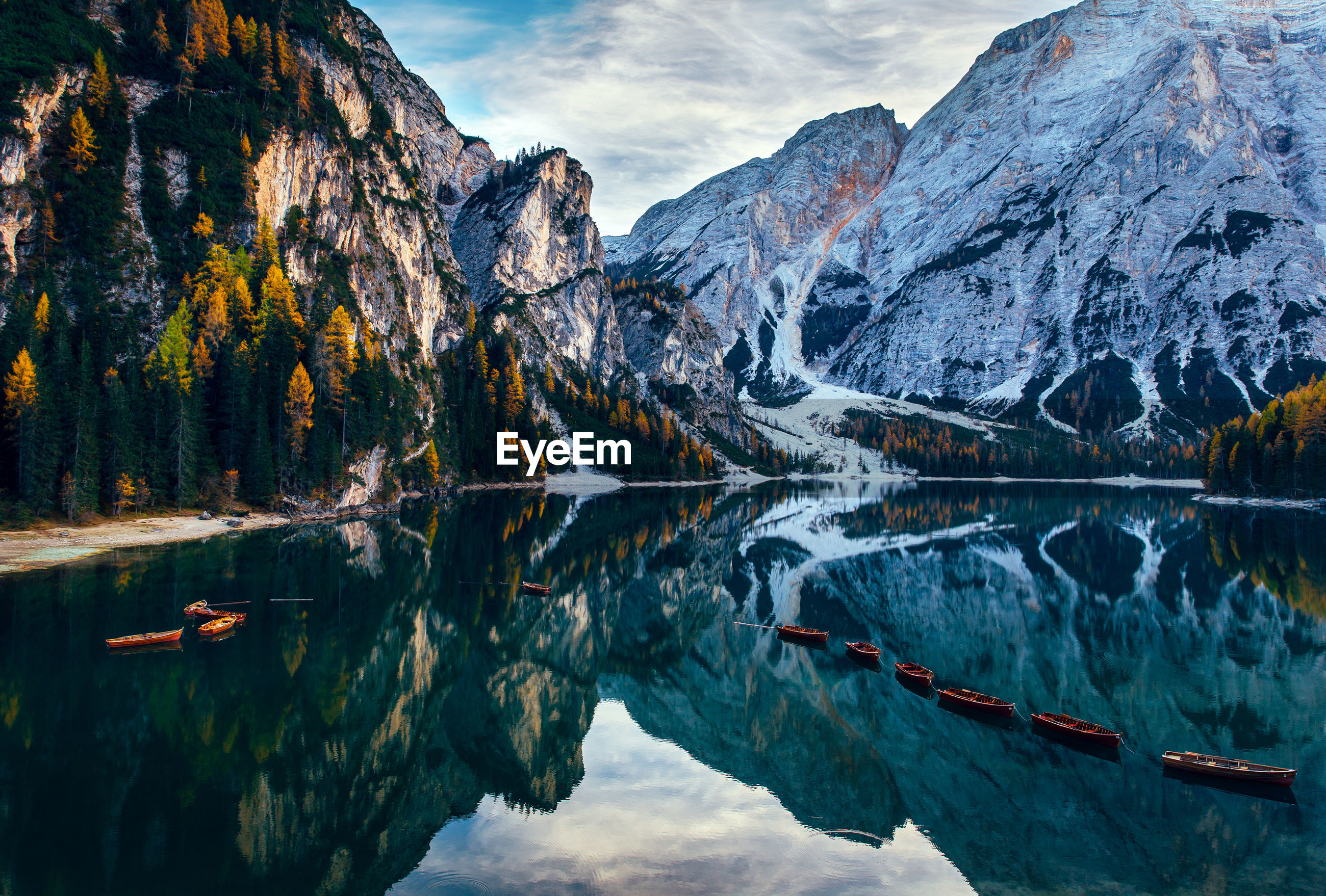 Boats in lake against snowcapped mountains