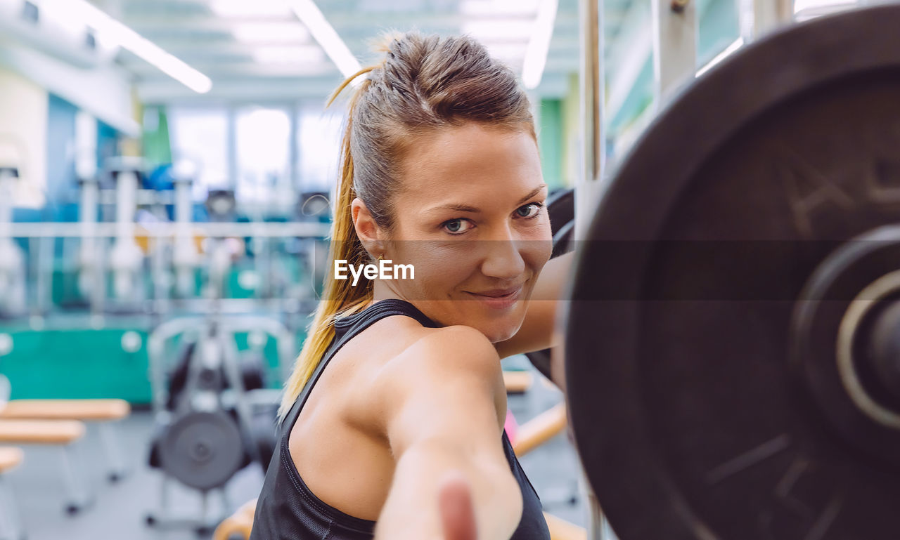 Portrait of woman lifting barbell in gym