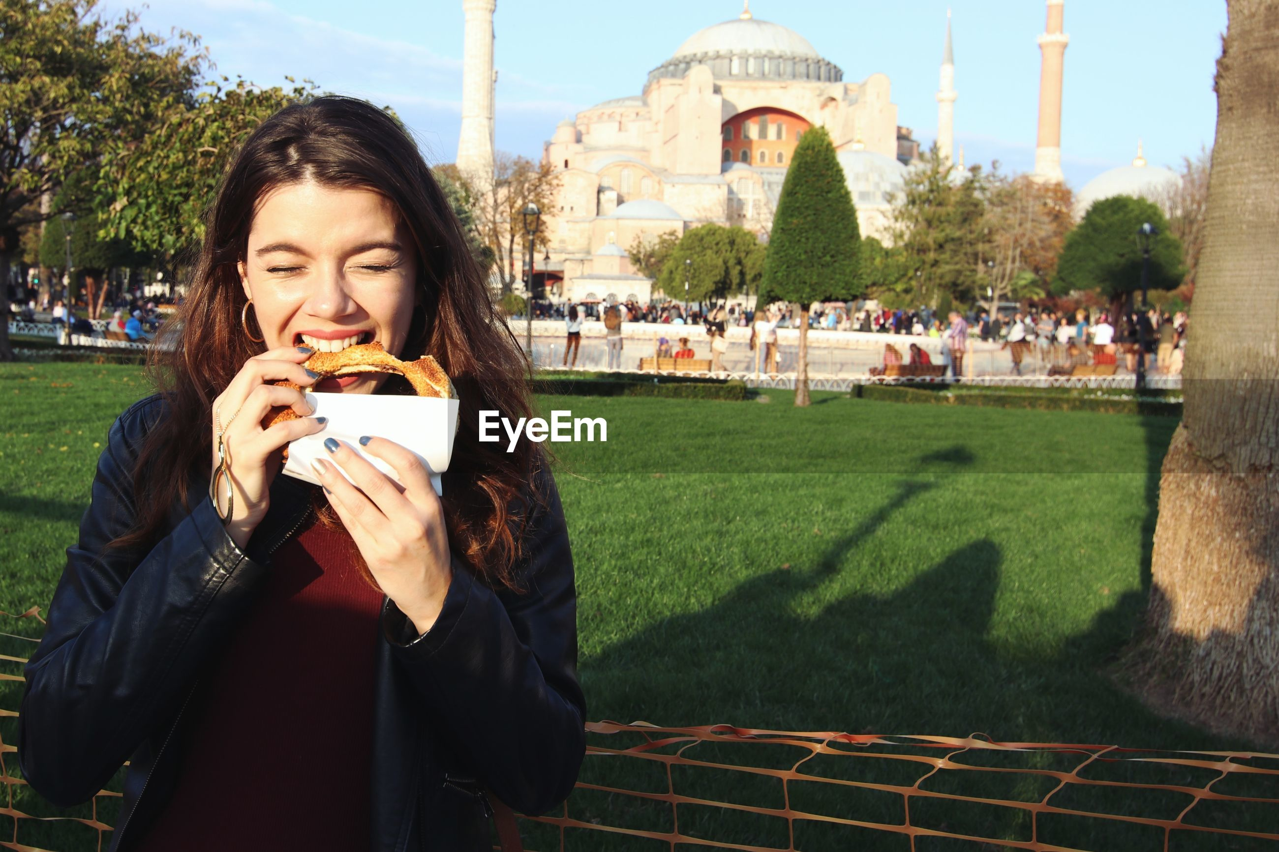 Portrait of young woman tourist eating in istanbul, turkey.