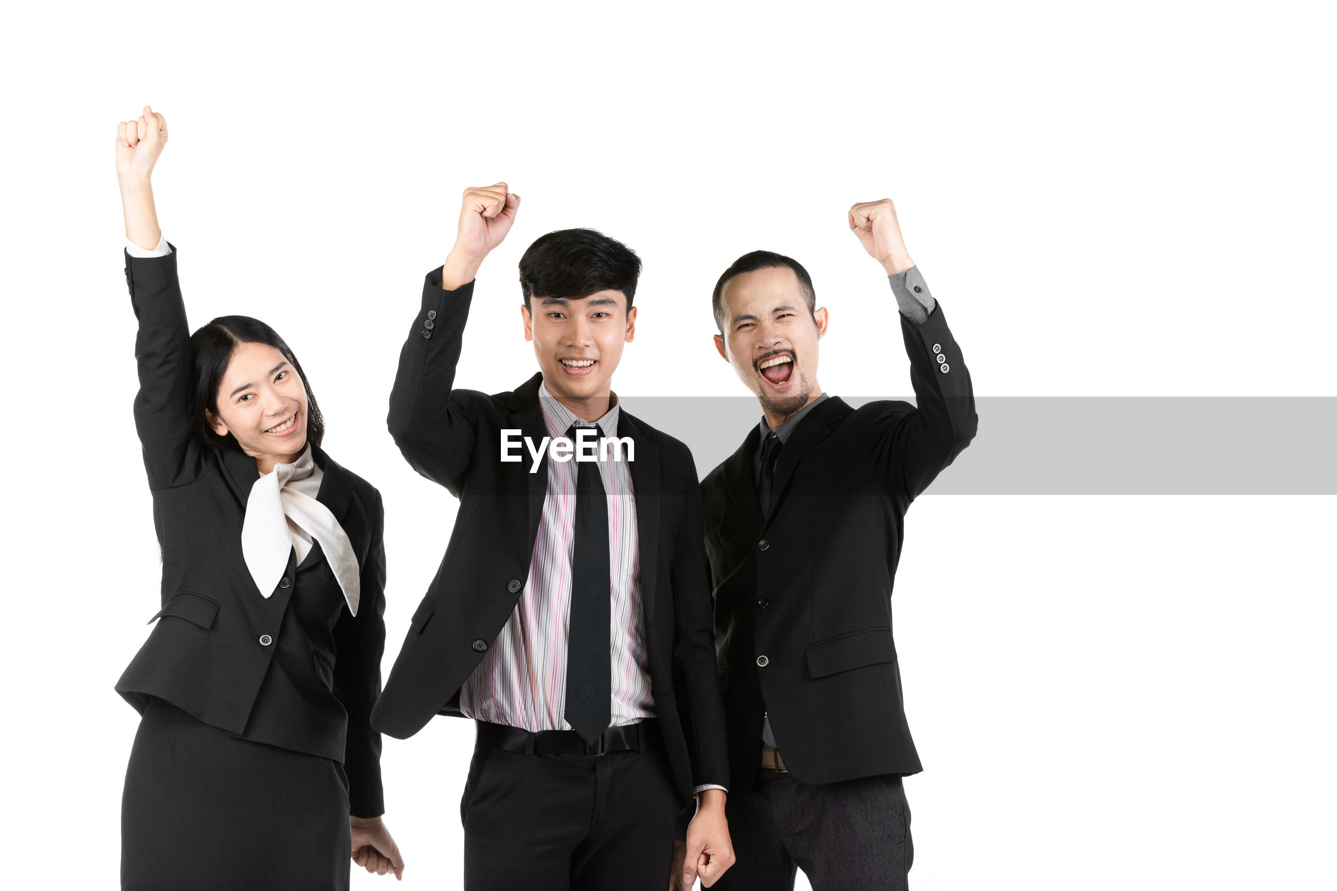 Portrait of smiling businessmen and businesswoman clenching fists against white background