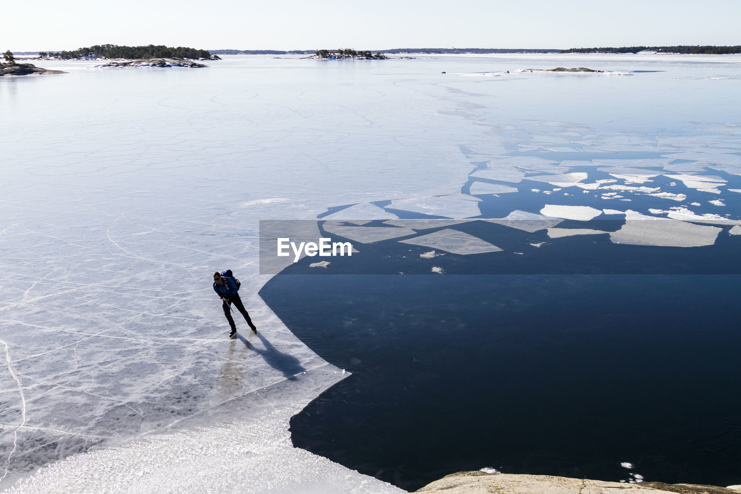 HIGH ANGLE VIEW OF WOMAN ON FROZEN LAKE