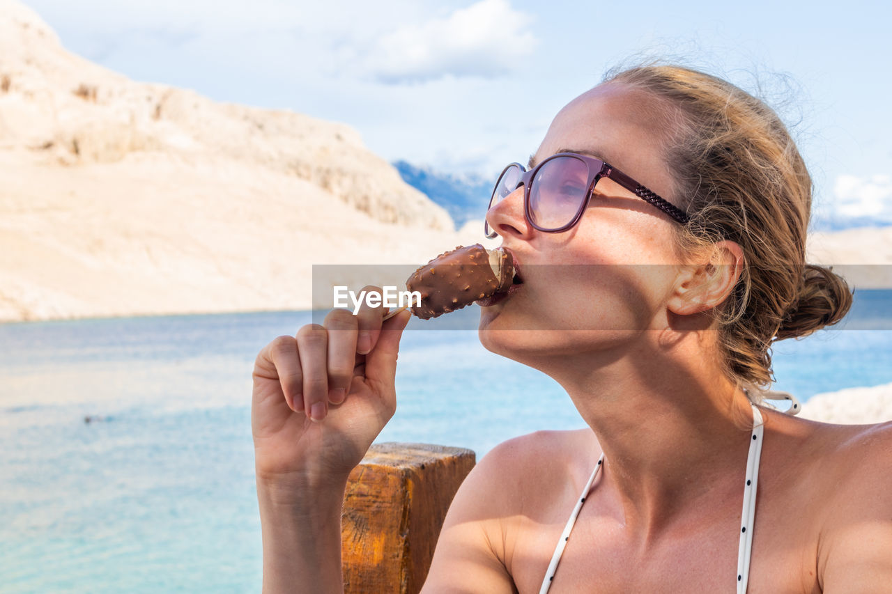 Close-up of woman eating ice cream by lake