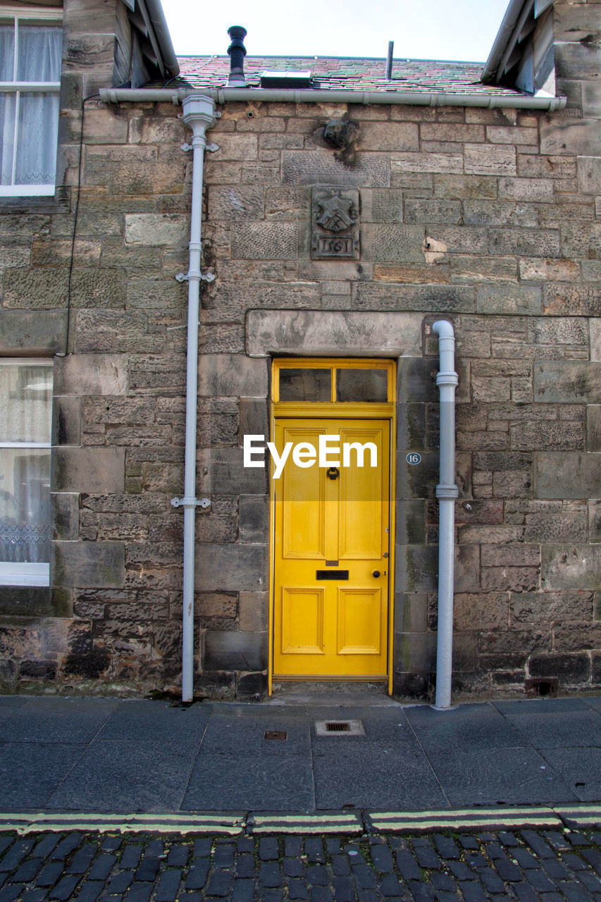 door, entrance, architecture, built structure, building exterior, building, day, no people, closed, house, city, outdoors, doorway, residential district, window, yellow, front door, wall, wall - building feature, security