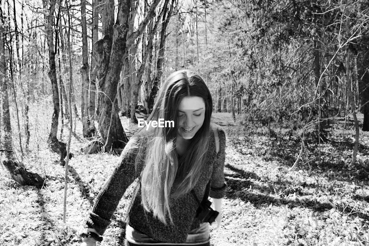 Smiling young woman standing in forest during sunny day
