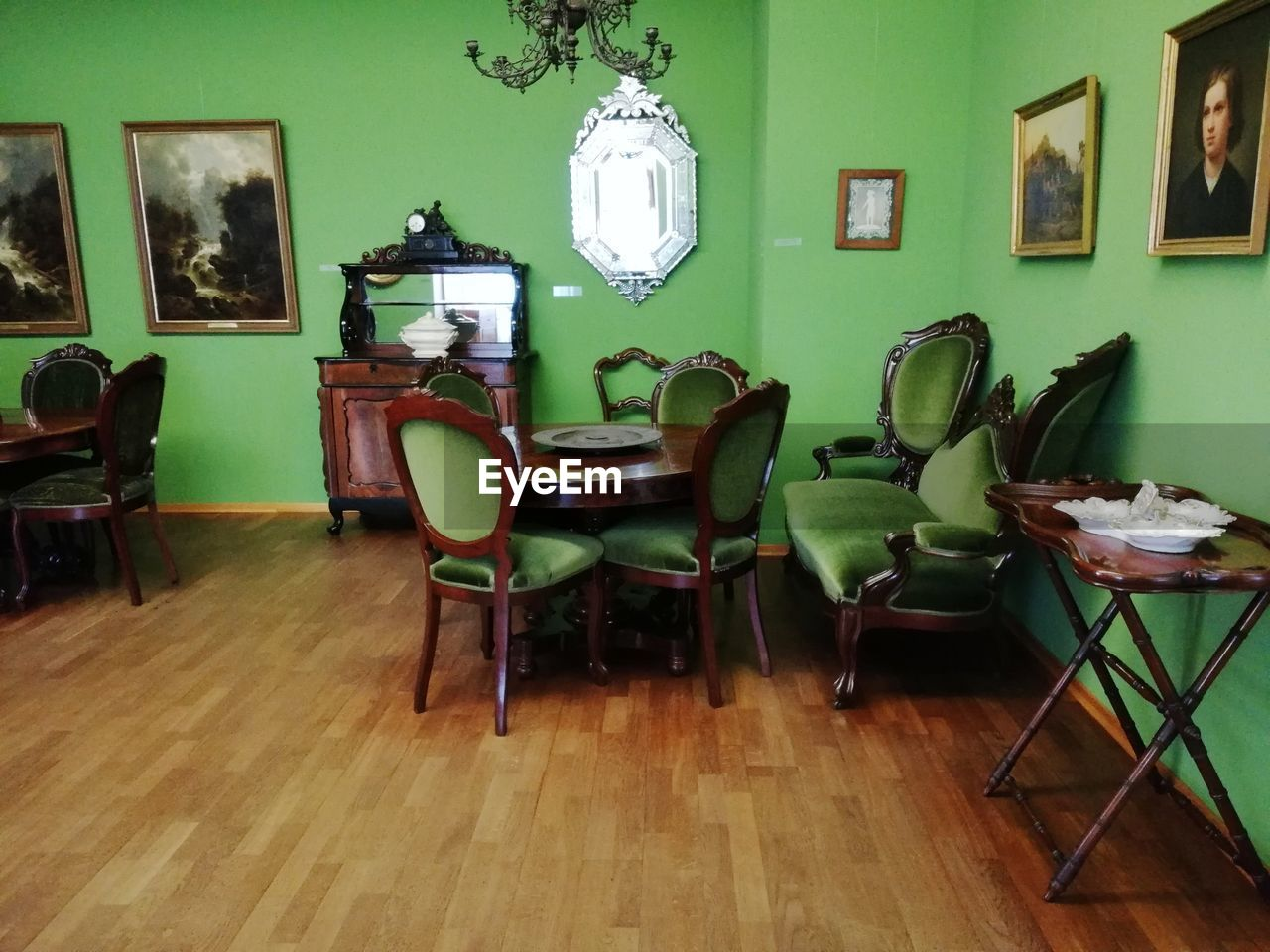 seat, chair, flooring, indoors, table, home interior, wood, hardwood floor, absence, no people, furniture, domestic room, frame, wall - building feature, lighting equipment, wood - material, living room, picture frame, green color, plant, electric lamp