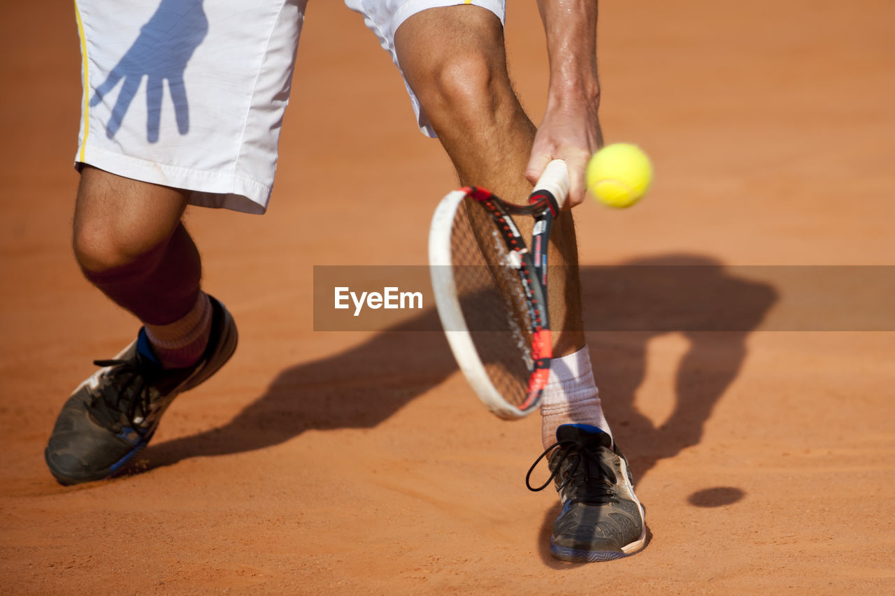 Low section of man playing tennis at court