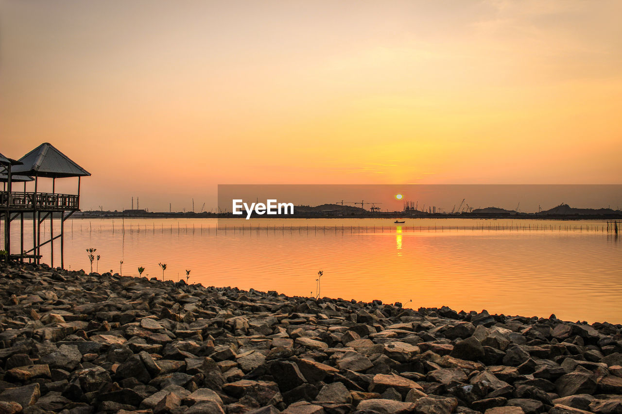 water, sky, sunset, scenics - nature, beauty in nature, orange color, tranquil scene, tranquility, solid, nature, architecture, built structure, rock, rock - object, lake, no people, non-urban scene, reflection, idyllic, sun, outdoors, groyne