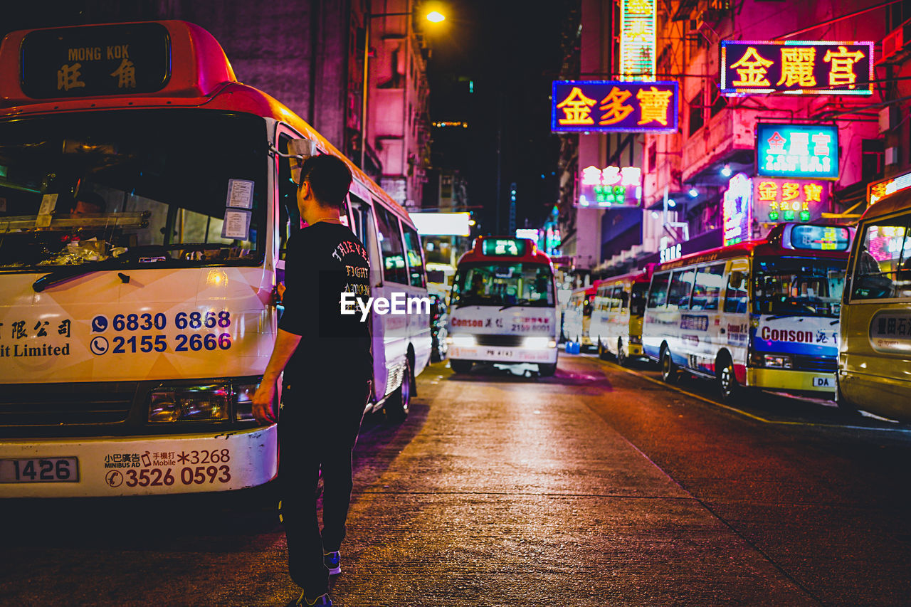 city, night, illuminated, street, architecture, real people, transportation, mode of transportation, land vehicle, city life, one person, car, built structure, motor vehicle, building exterior, lifestyles, rear view, walking, full length, city street, outdoors