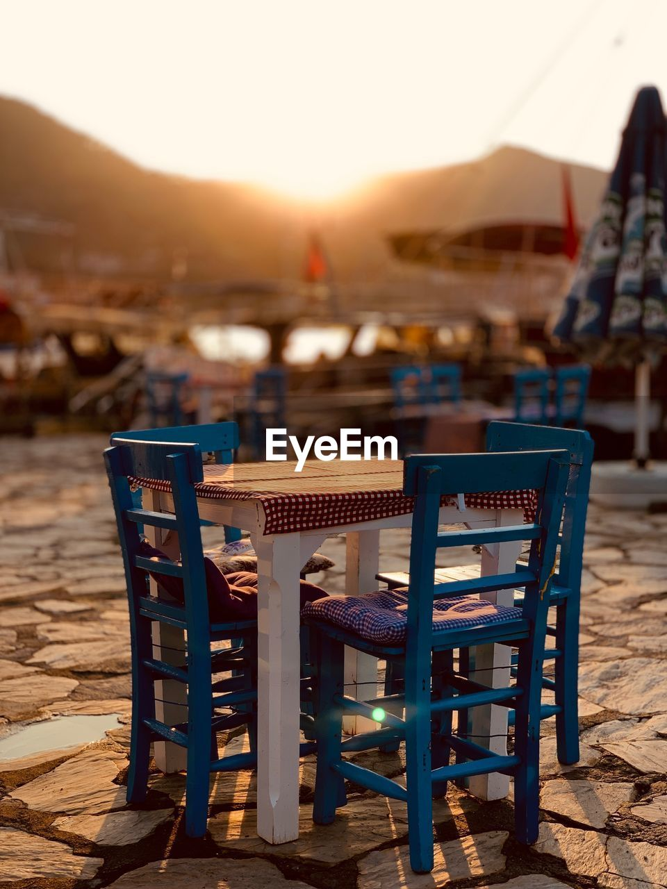 chair, table, water, seat, land, sky, beach, nature, wood - material, architecture, focus on foreground, business, sea, absence, clear sky, empty, restaurant, sand, relaxation, outdoors, no people, setting