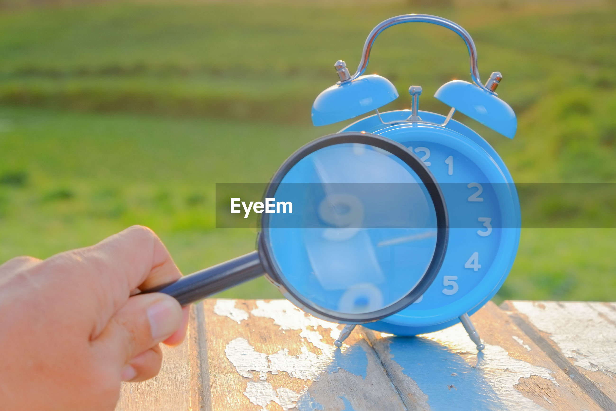 Cropped hand holding magnifying glass by alarm clock on field