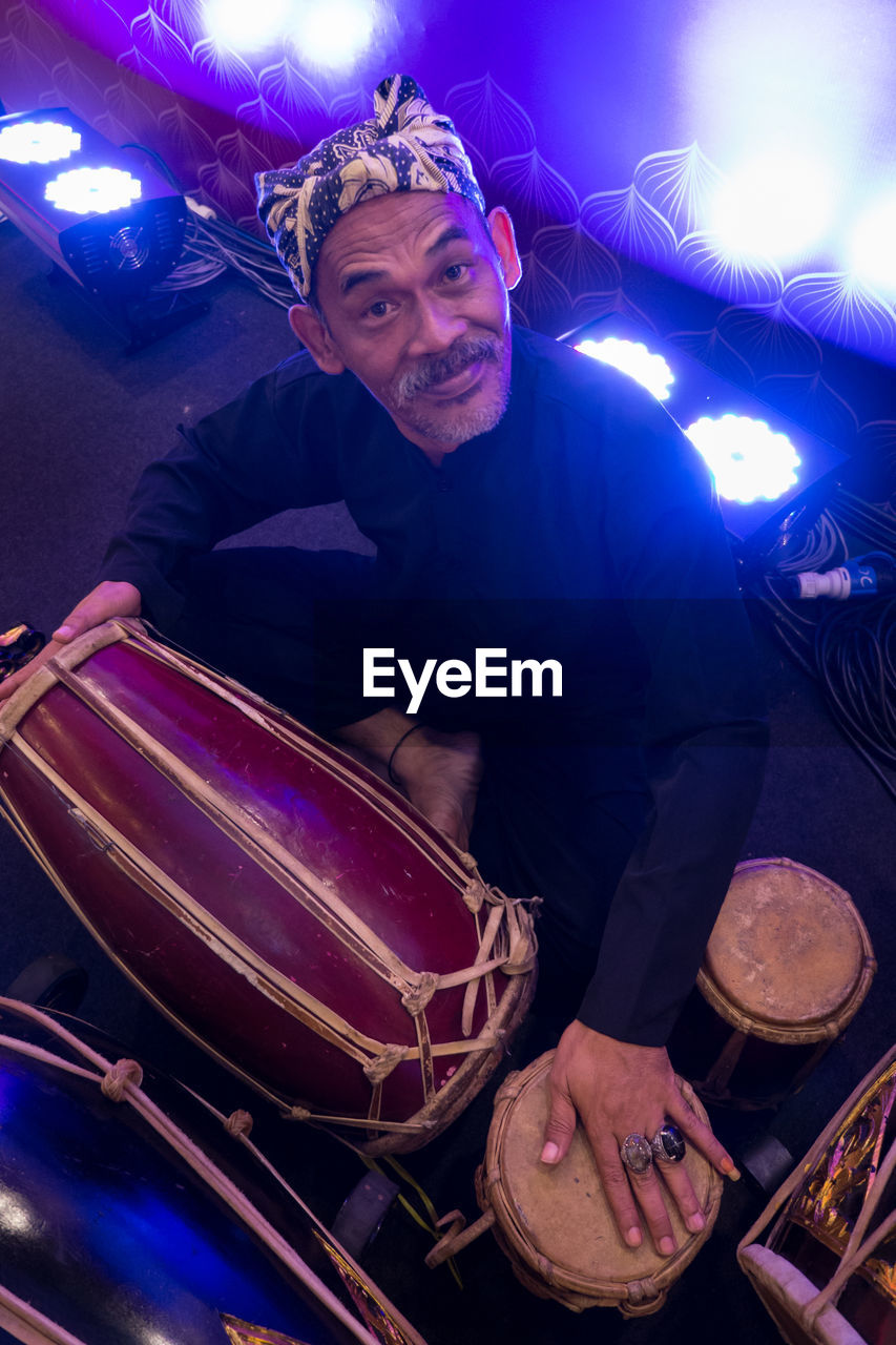 arts culture and entertainment, music, drum - percussion instrument, one person, illuminated, drum kit, real people, drumstick, musical instrument, drummer, musician, nightlife, playing, indoors, night, looking at camera, skill, portrait, performance, occupation, popular music concert, young adult, people