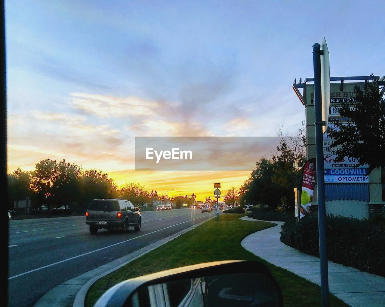 car, land vehicle, transportation, mode of transport, sunset, road, sky, cloud - sky, no people, tree, outdoors, city, road sign, architecture, day