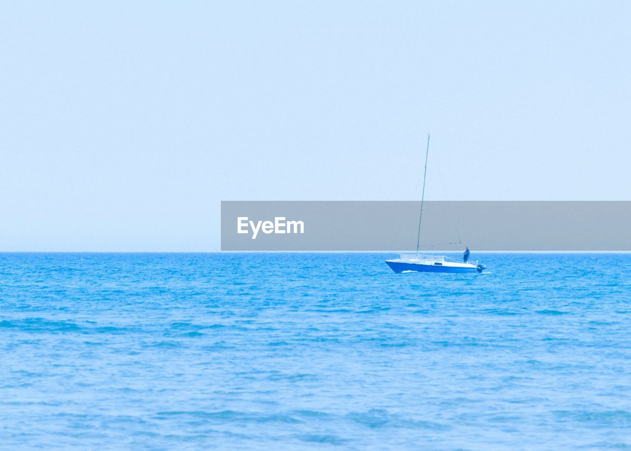 Scenic view of motorboat in ocean against clear sky