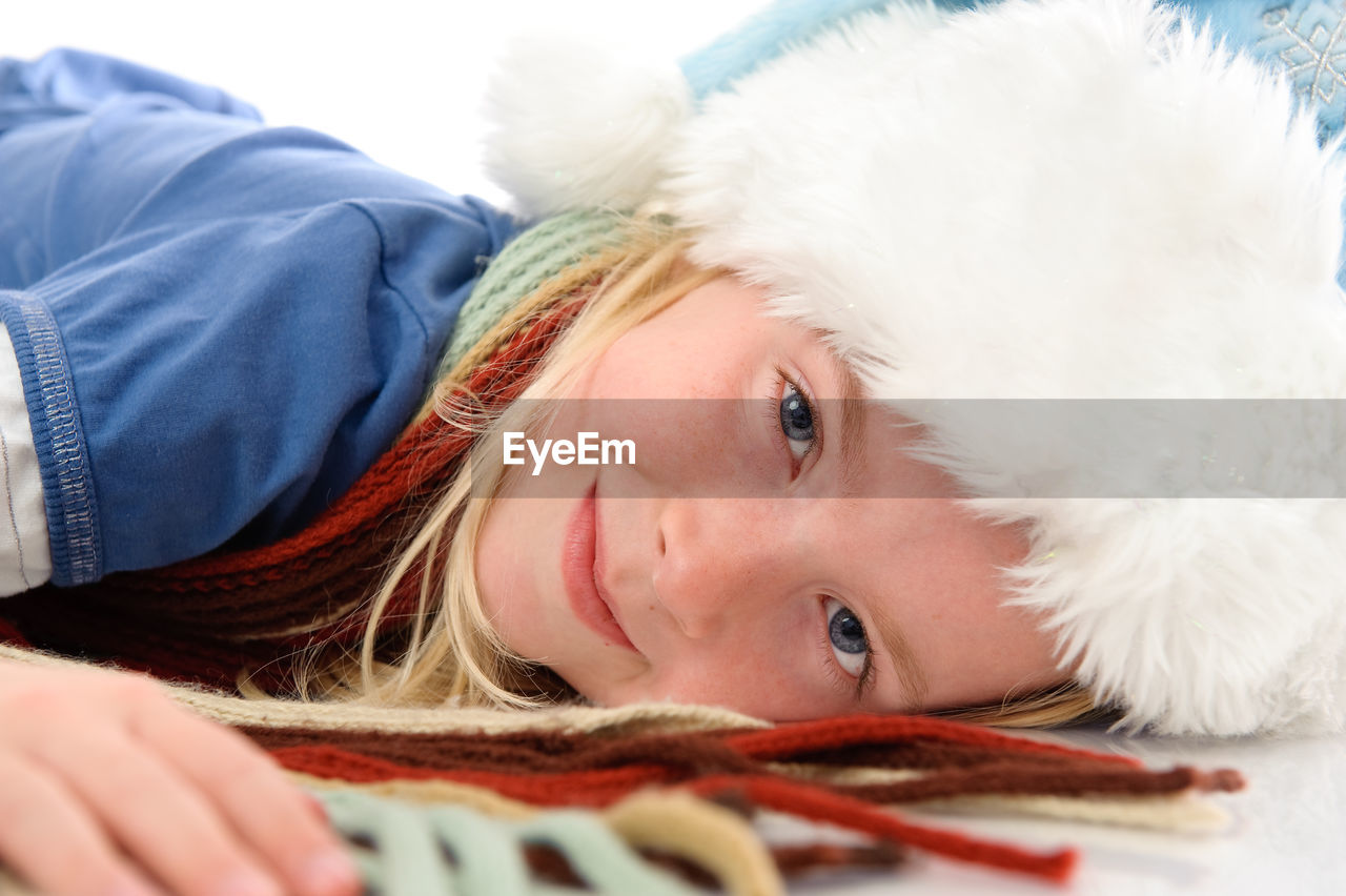 CLOSE-UP PORTRAIT OF CUTE GIRL LYING IN HAT
