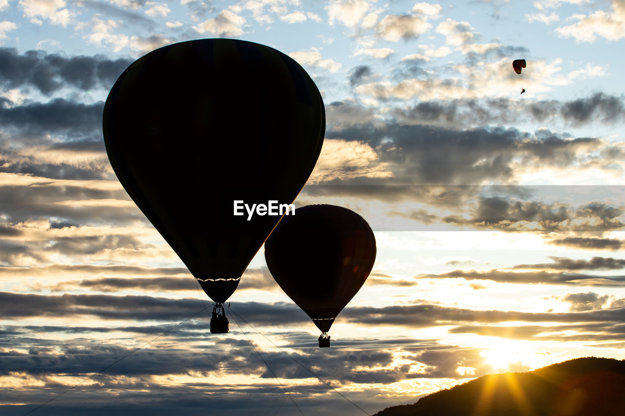 sky, cloud - sky, balloon, hot air balloon, air vehicle, sunset, flying, transportation, nature, mid-air, scenics - nature, beauty in nature, no people, mode of transportation, orange color, sun, silhouette, outdoors, tranquil scene, tranquility, ballooning festival