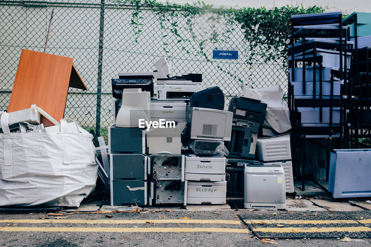 Abandoned Stacked Computer Printers Against Fence