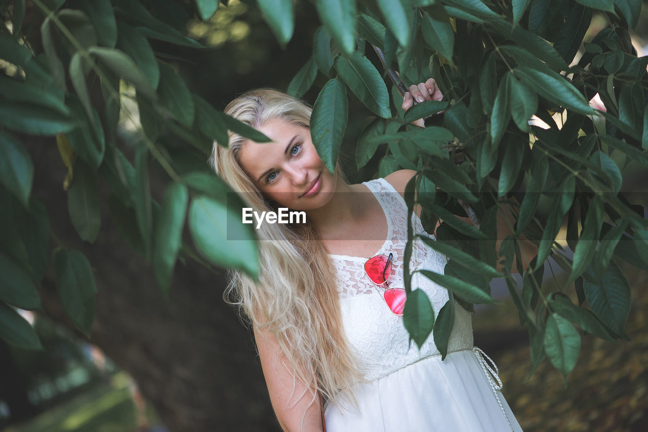 Young Woman Smiling By Tree