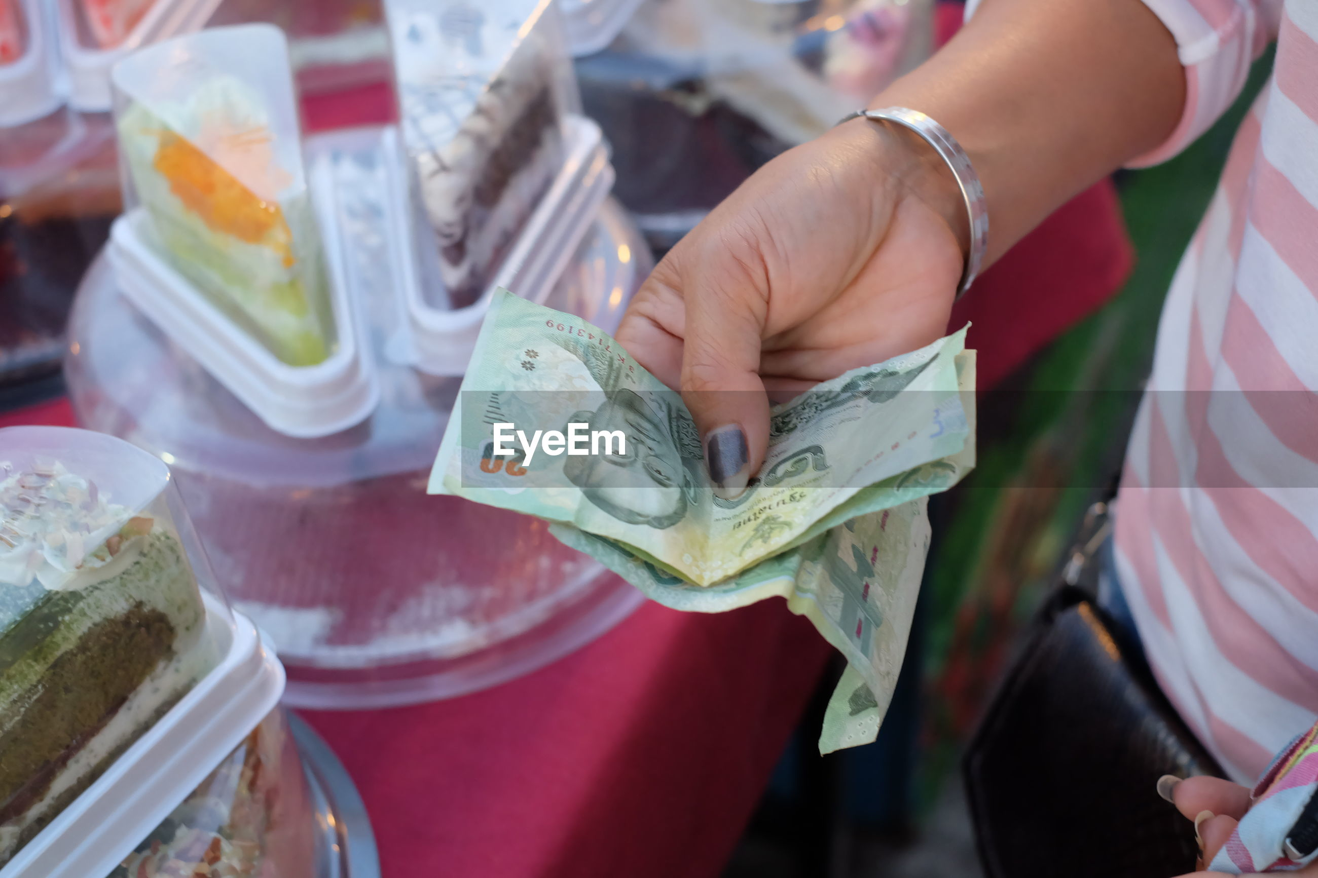 Midsection of woman holding paper currency at market