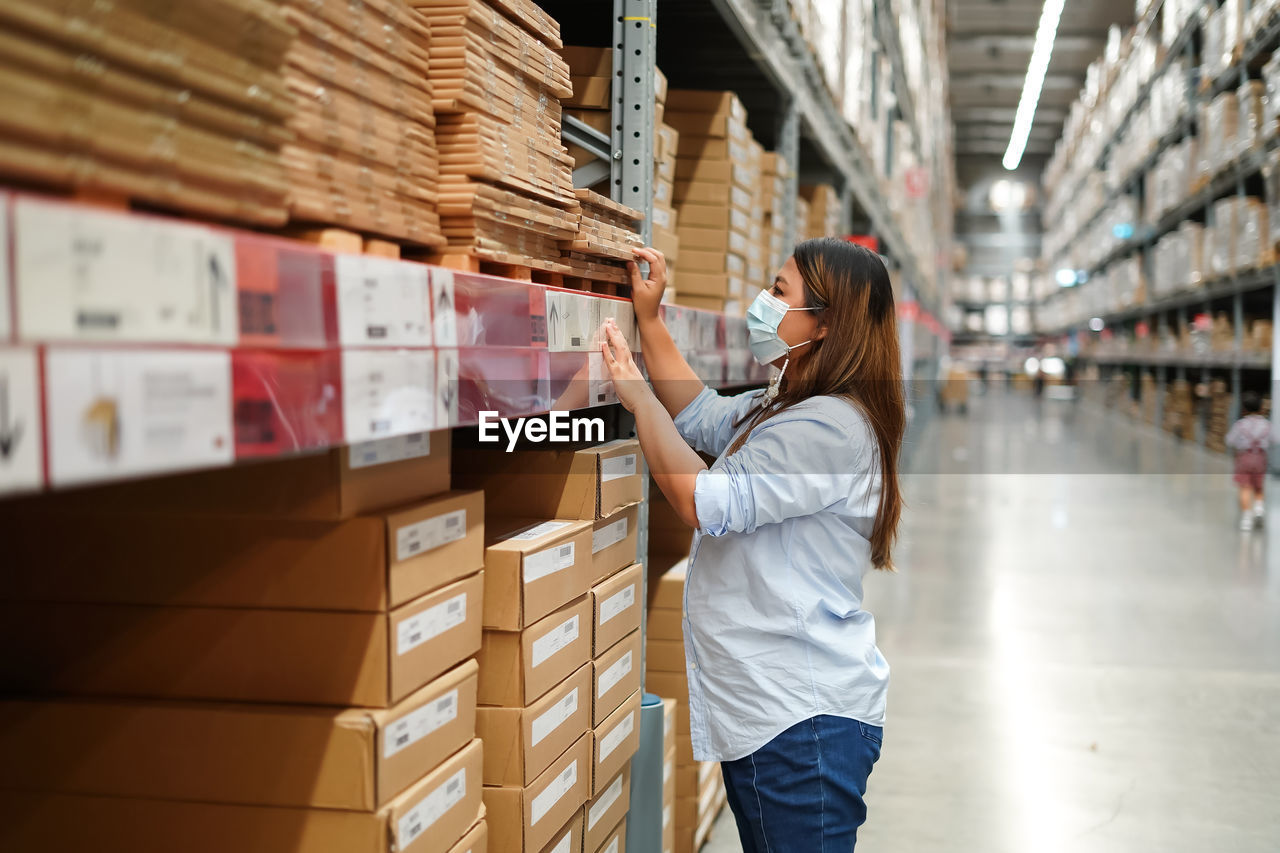 Side view of woman standing at warehouse