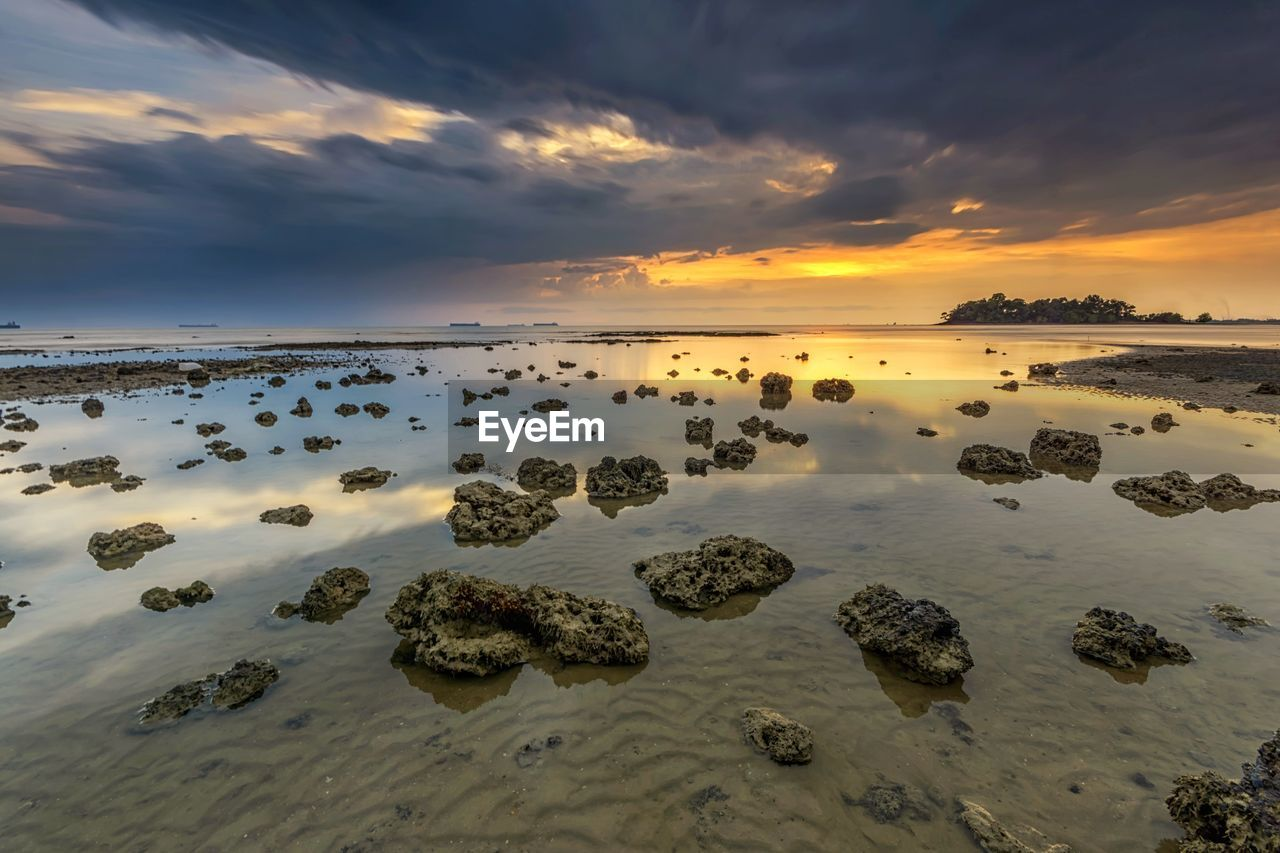 sunset, sky, scenics - nature, cloud - sky, beauty in nature, tranquility, tranquil scene, water, sea, rock, idyllic, land, rock - object, no people, beach, non-urban scene, solid, nature, orange color, horizon over water, salt flat