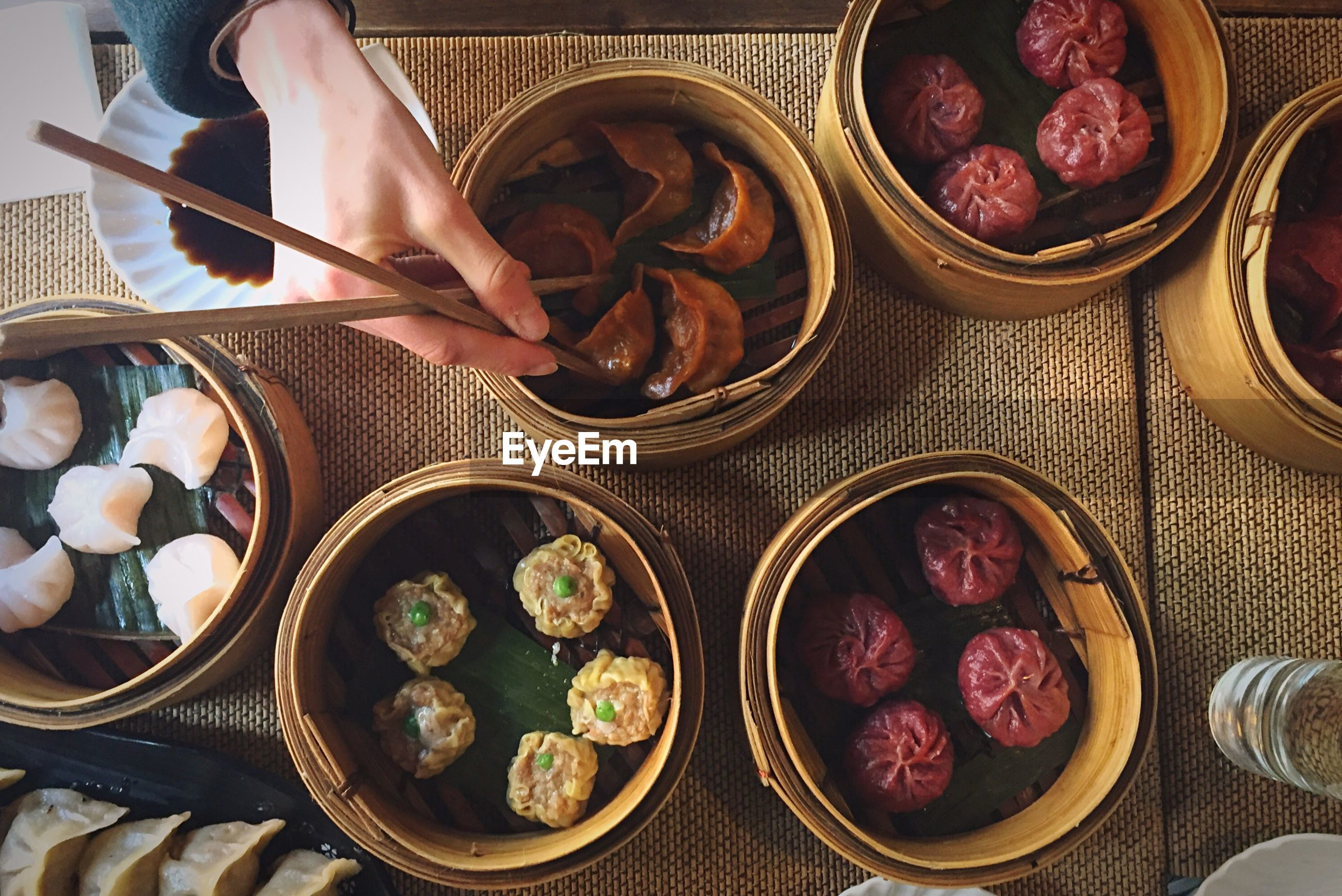 Directly above shot of hand holding food in bamboo steamer
