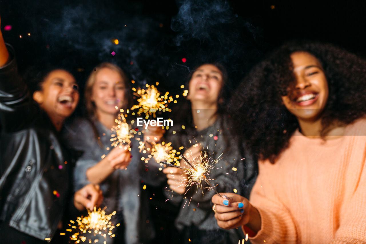 Friends enjoying sparklers at night