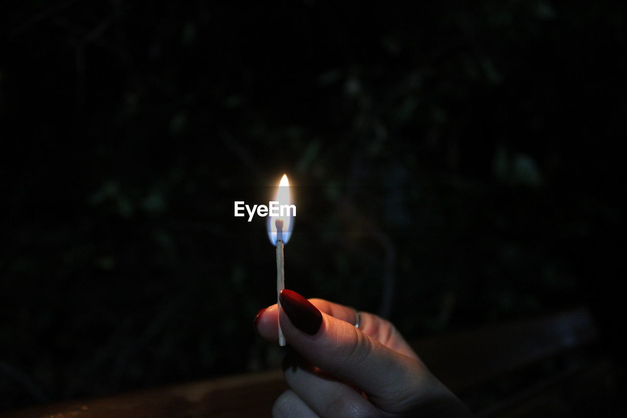PERSON HAND HOLDING LIT CANDLE