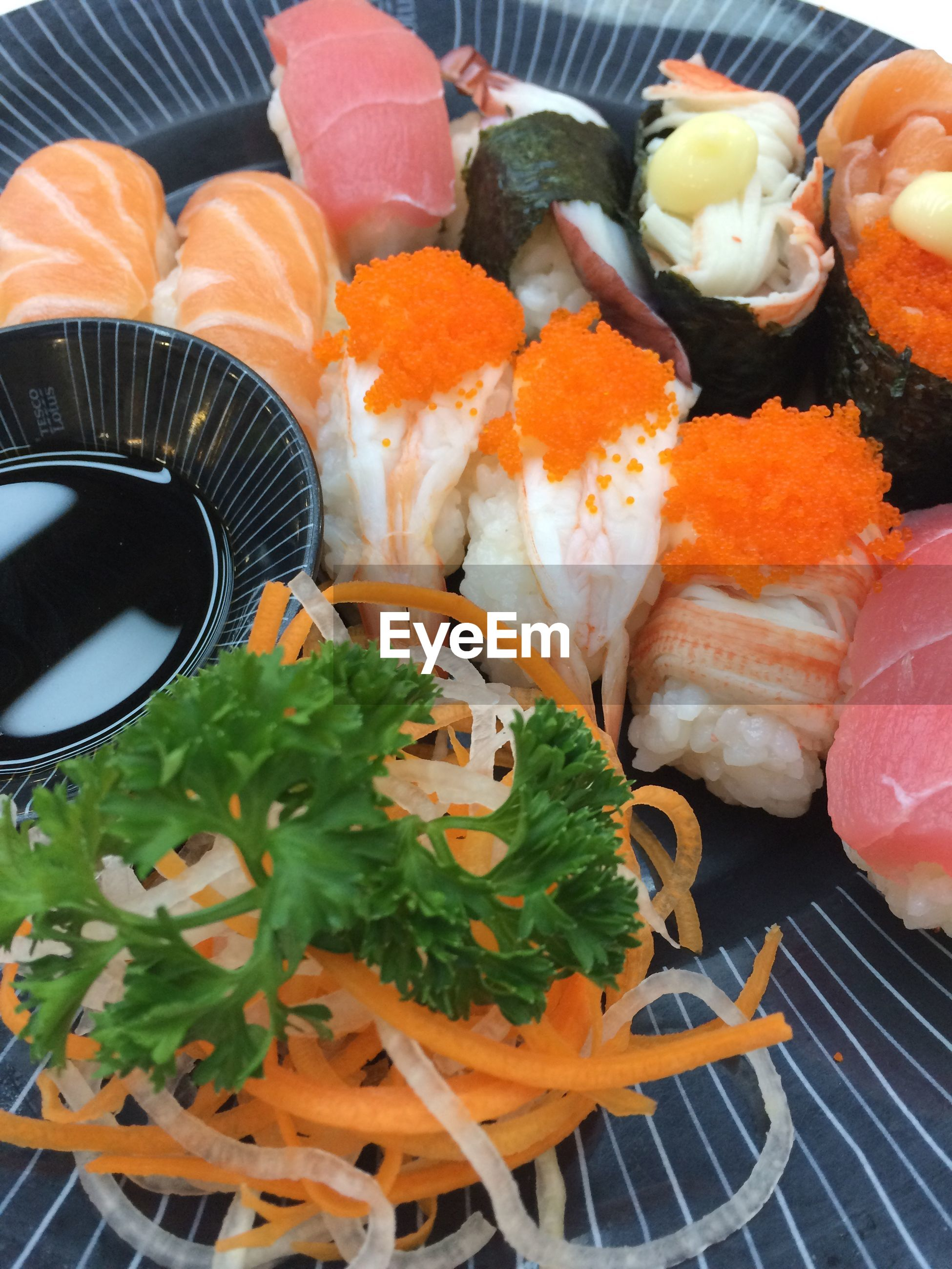 High angle view of sushi served with dip in plate