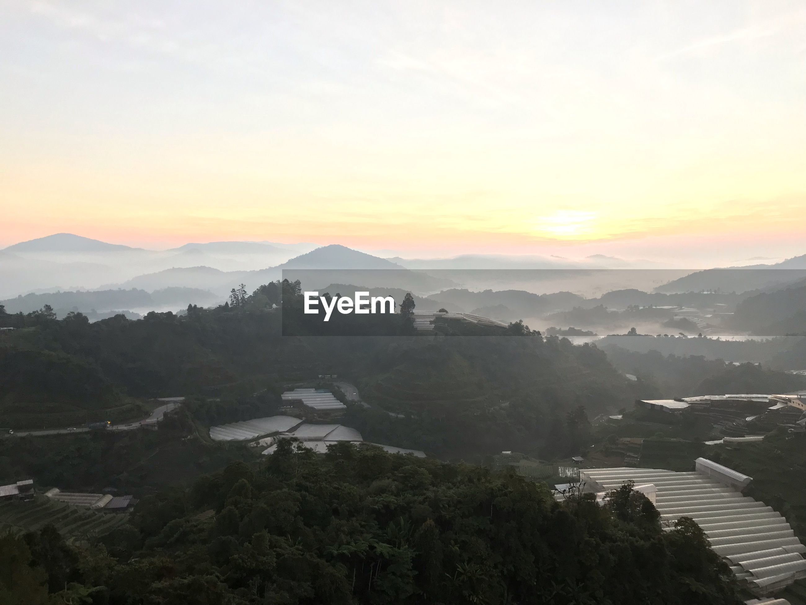 HIGH ANGLE VIEW OF MOUNTAIN RANGE AGAINST SKY DURING SUNSET