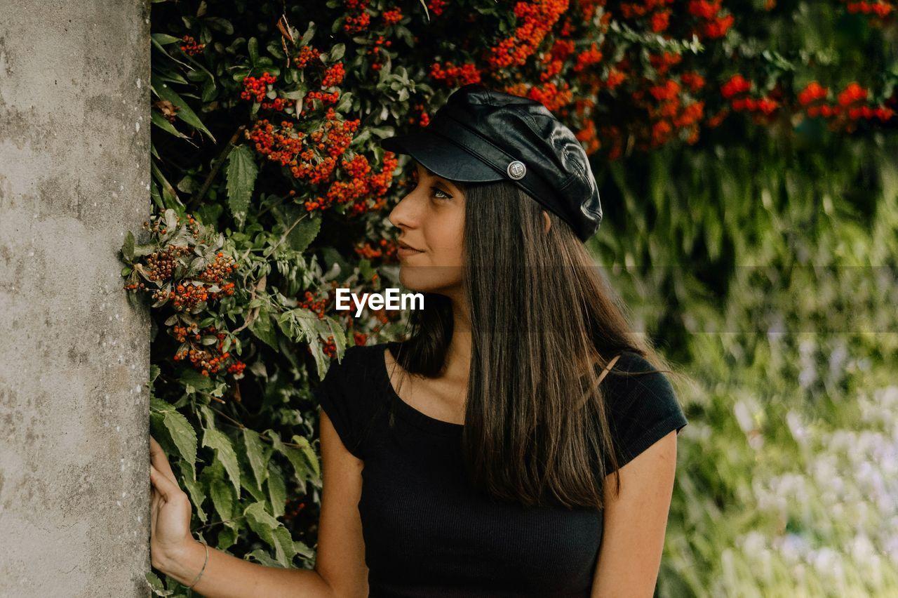 Woman In Cap Looking Away Against Flowering Plants