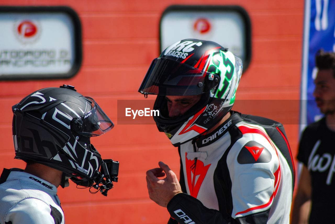 helmet, headwear, two people, security, people, sport, protection, clothing, focus on foreground, real people, waist up, men, portrait, close-up, sports helmet, red, day, holding, headshot