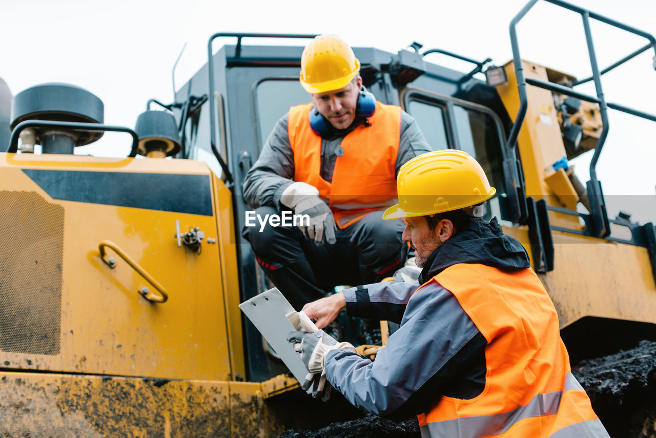 People working on construction vehicle against sky