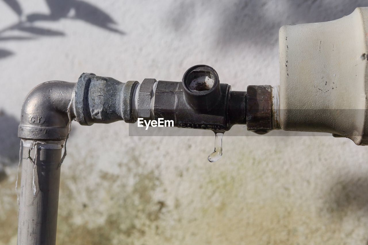 metal, close-up, no people, focus on foreground, faucet, pipe - tube, day, connection, old, outdoors, rusty, high angle view, water, valve, wall - building feature, nature, water pipe, control, pipe, machine valve, running water