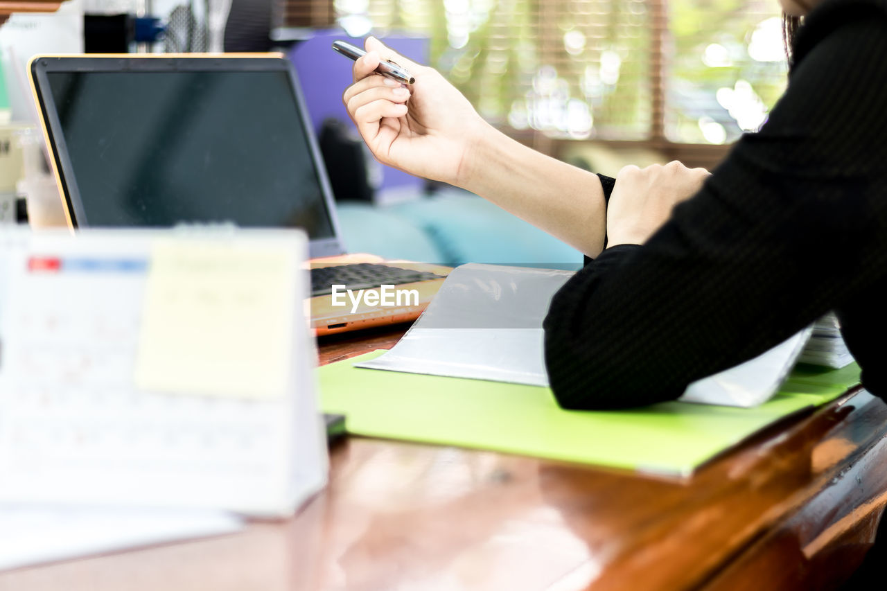 Midsection of businesswoman with file on desk sitting in office