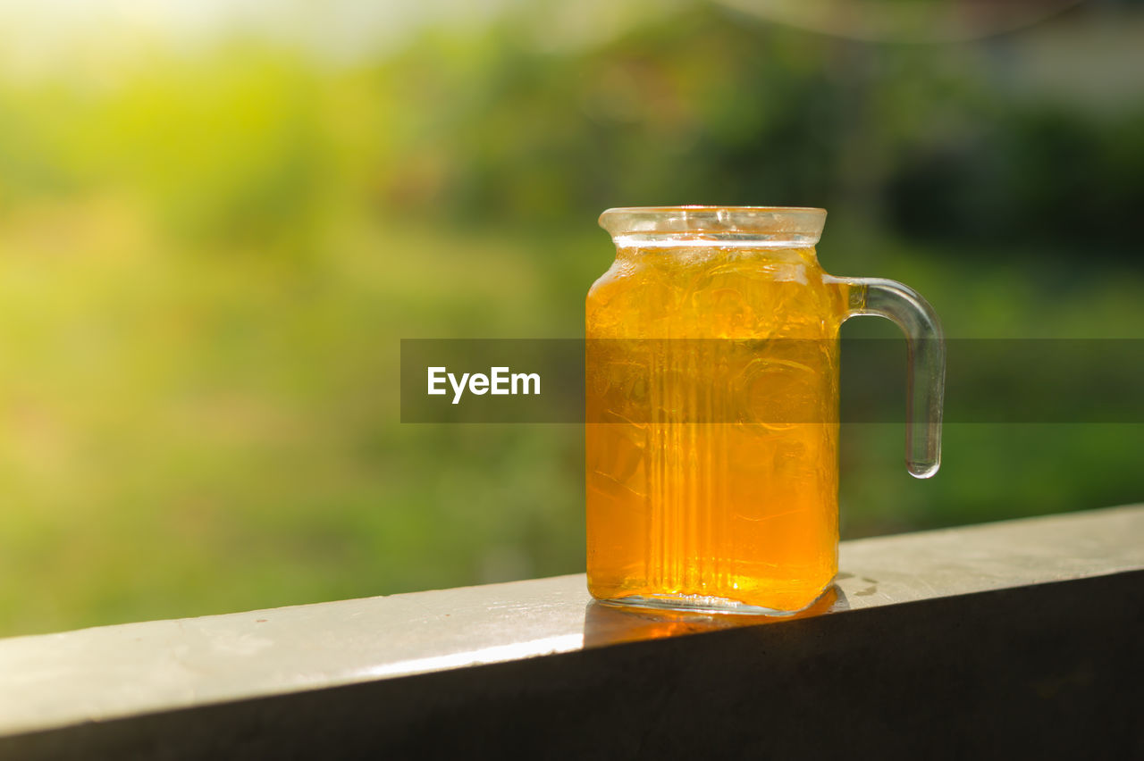 Close-Up Of Orange Juice In Glass Jar On Railing
