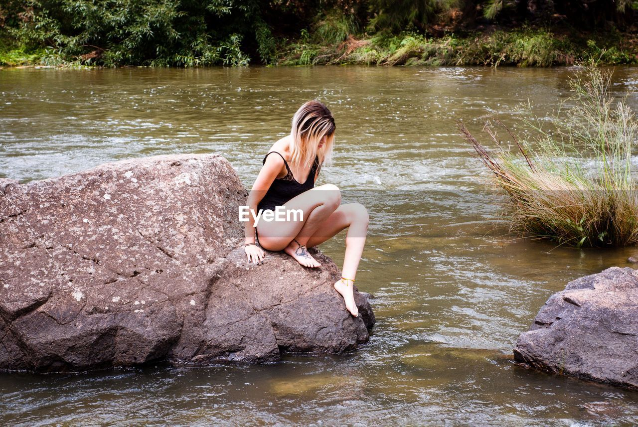 Woman sitting on rock at river