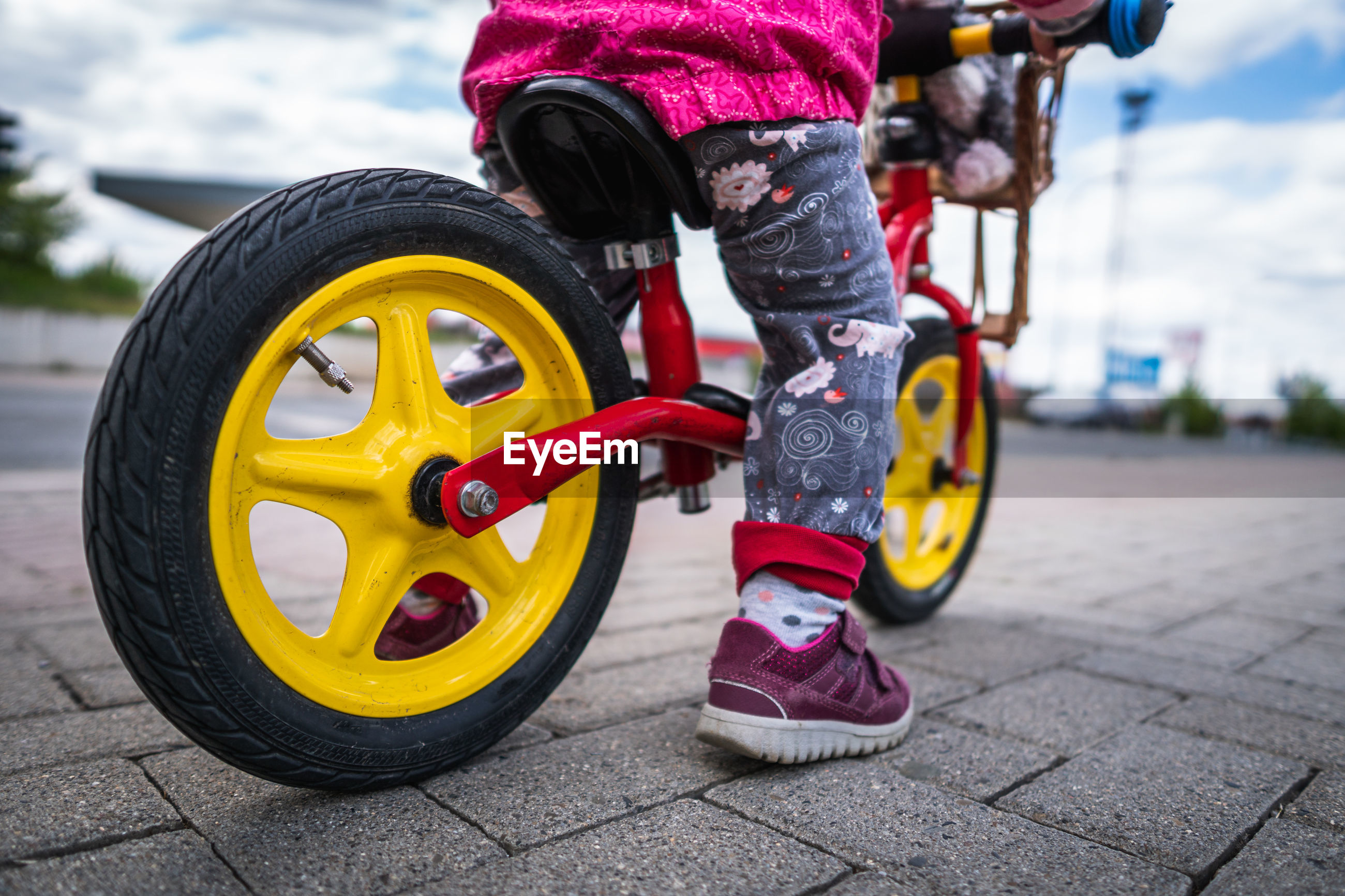 bicycle, transportation, vehicle, wheel, sports, one person, childhood, city, mode of transportation, child, helmet, cloud, street, bicycle wheel, activity, tire, day, outdoors, sports equipment, headwear, men, full length, yellow, cycling, sky, lifestyles, riding, adult, nature, leisure activity, land vehicle, footpath, pedal, motorcycle, sports helmet, person, bmx bike, motion, auto part
