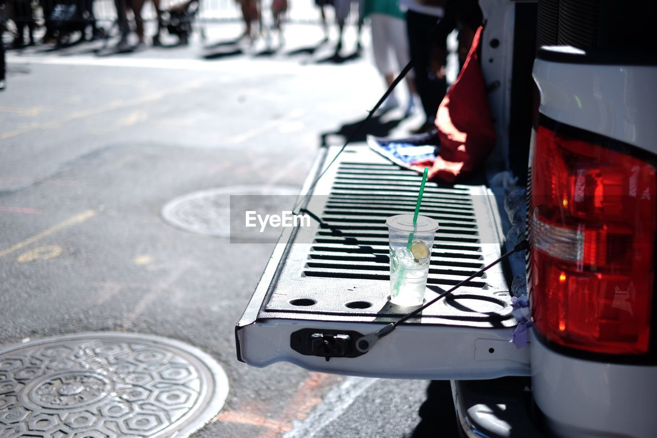 High angle view of drink on car trunk at street