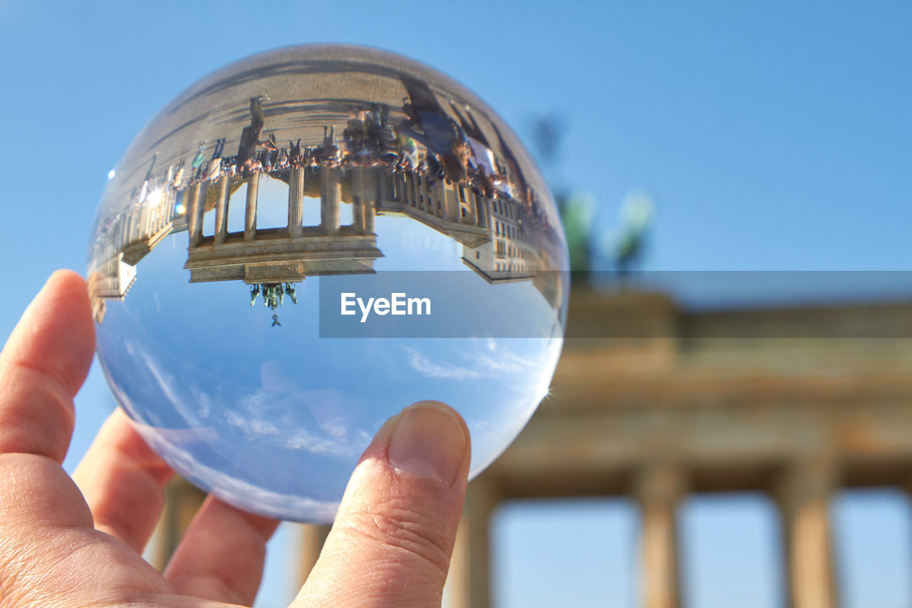 Close-up of hand holding crystal ball against brandenburg gate