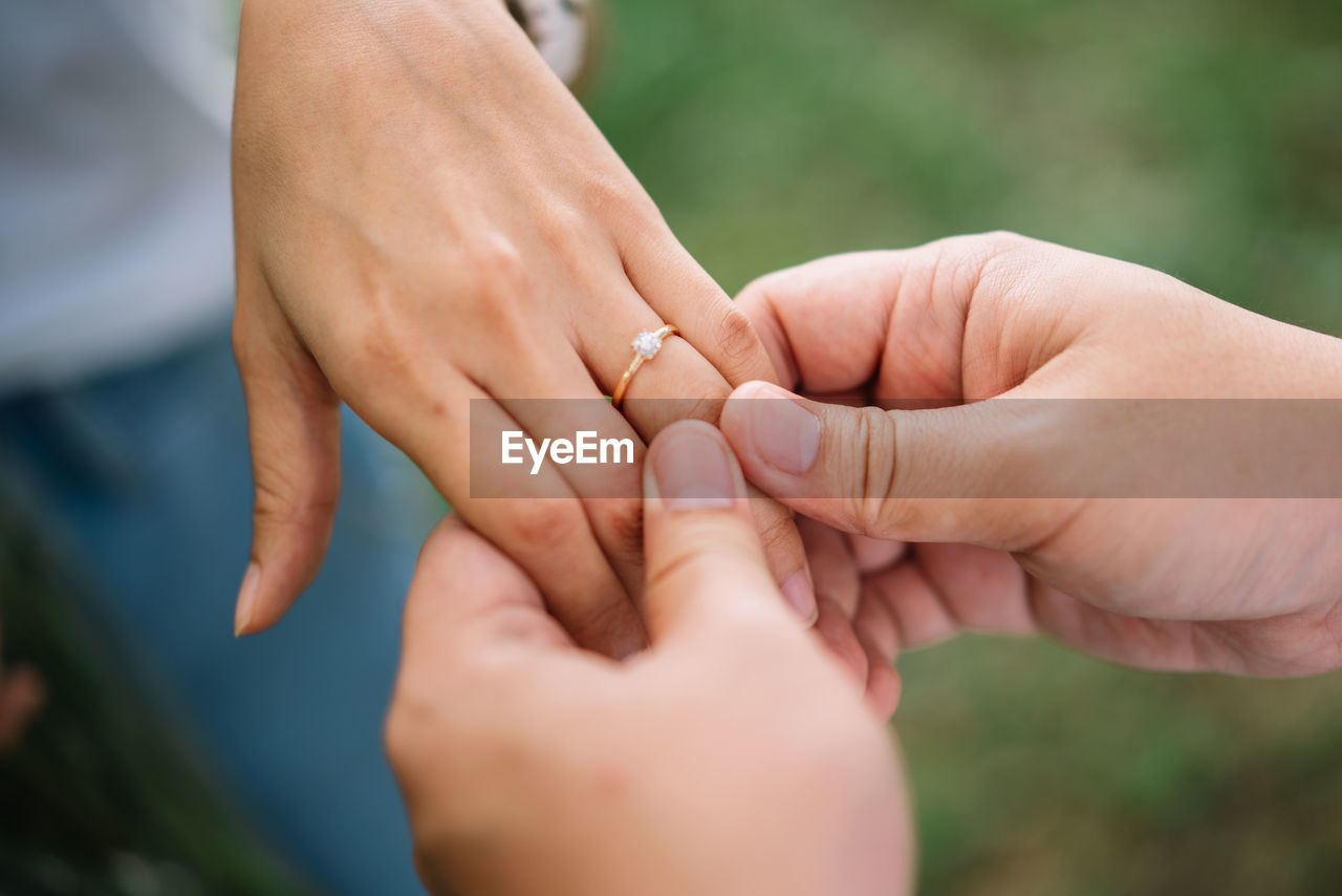 human hand, hand, human body part, two people, love, women, ring, adult, jewelry, positive emotion, couple - relationship, body part, bonding, togetherness, real people, celebration, wedding ring, finger, focus on foreground, men, husband, wife, wedding ceremony