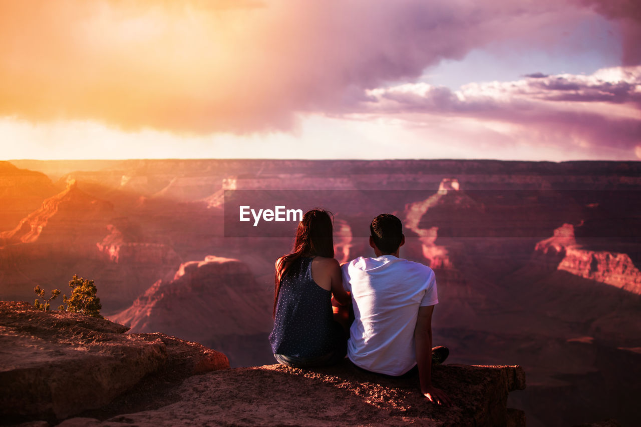 Rear View Of Couple Sitting On Cliff Against Sky During Sunset