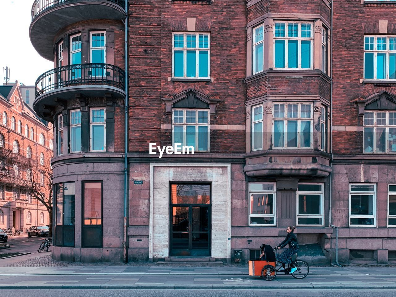 building exterior, built structure, architecture, window, city, transportation, building, street, residential district, mode of transportation, day, real people, land vehicle, outdoors, scooter, glass - material, people, bicycle, road, entrance, apartment