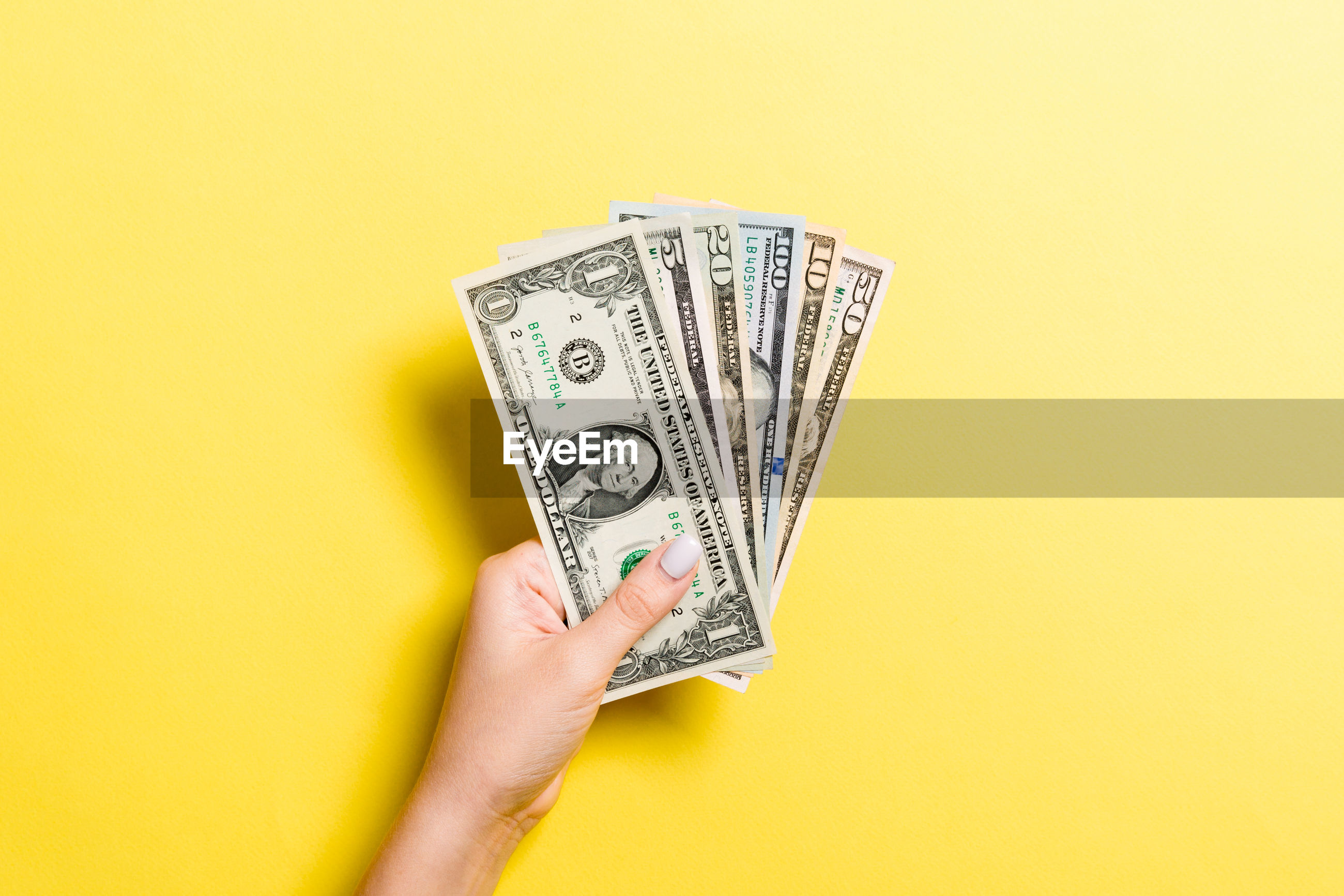 Cropped hand holding paper currencies on yellow background