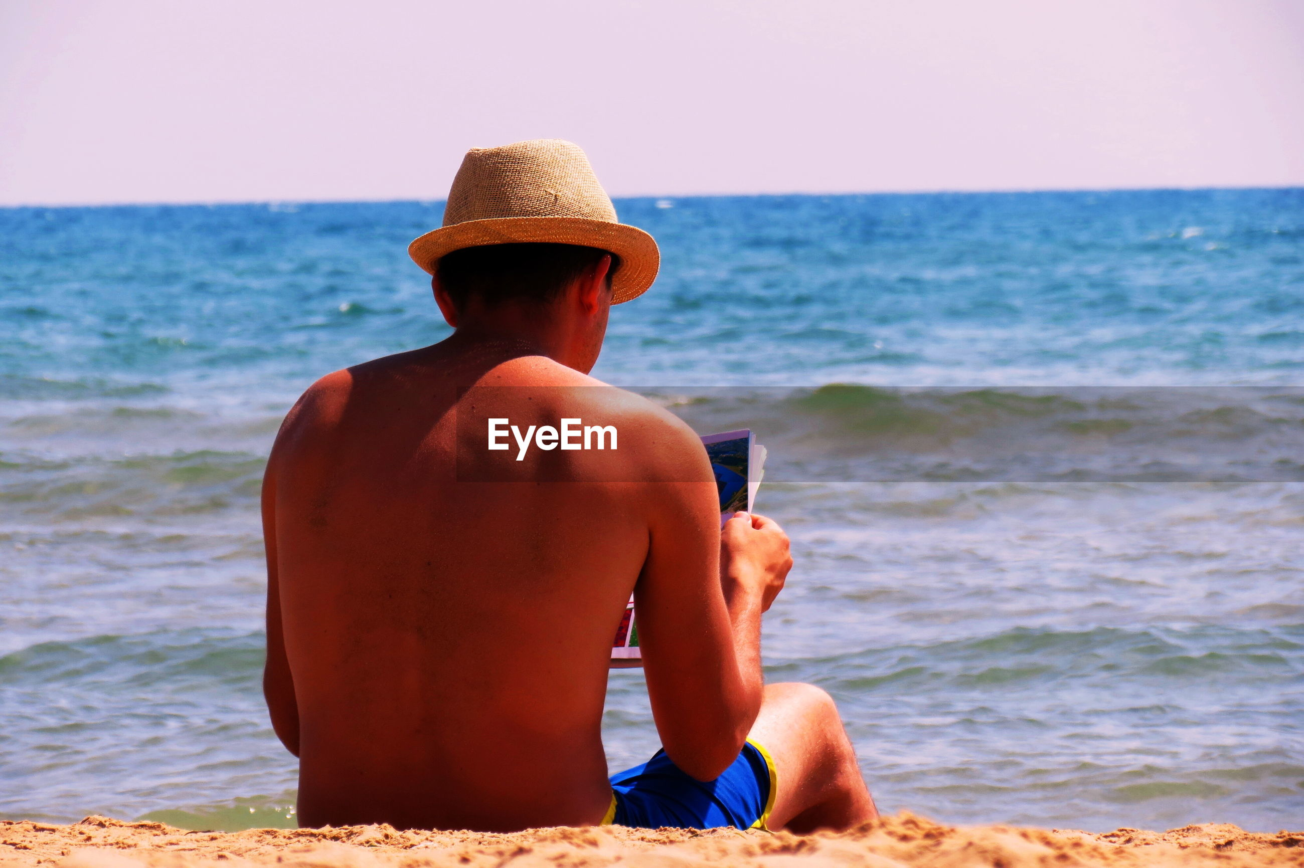 Rear view of shirtless man with magazine while relaxing on shore at beach