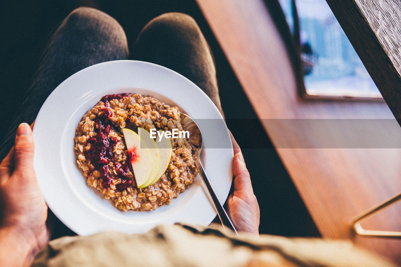 Midsection Of Person Holding Porridge On Plate On Lap